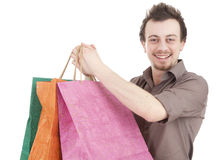 Happy young man with coloured shopping bags Stock Images