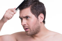 Happy young man combing hair. Stock Photo