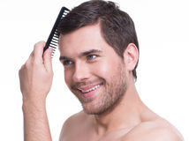 Happy young man combing hair. Stock Images
