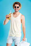 Happy young man with cooler bag standing and drinking beer Stock Image