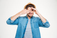 Happy young man covered one eye with hand and smiling Royalty Free Stock Image