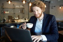 Video chatting. Happy young man with cup of tea working in front of laptop in cafe or watching curious video Royalty Free Stock Photo