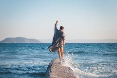 Happy young man dancing on the dock. At the beach Stock Image