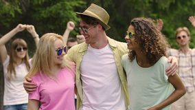 Happy young man dancing with two beautiful women at outdoor party, summer flirt. Stock footage stock footage