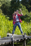 Happy young man dancing on wooden bridge for fun satisfaction royalty free stock photos