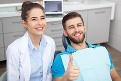 Happy young man in a dentist's chair giving a thumbs up. royalty free stock images