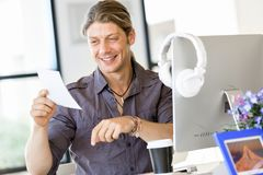 Happy young man designer working. Happy young man designer at his office workplace royalty free stock image