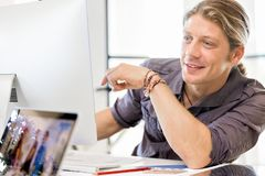 Happy young man designer working. Happy young man designer at his office workplace royalty free stock photos