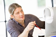 Happy young man designer working. Happy young man designer at his office workplace royalty free stock photography
