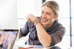 Happy young man designer working. Happy young man designer at his office workplace stock photography