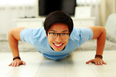 Happy young man doing push ups in the living room Royalty Free Stock Photos
