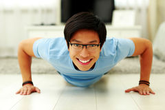 Happy young man doing push ups Stock Photos
