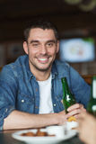 Happy young man drinking beer at bar or pub Royalty Free Stock Photos