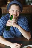 Happy young man drinking beer at bar or pub Royalty Free Stock Photography