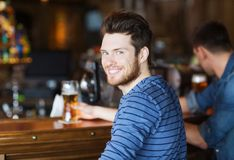 Happy young man drinking beer at bar or pub Stock Photography