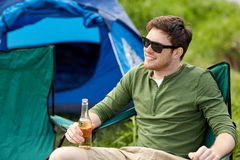 Happy young man drinking beer at campsite tent. Camping, travel, tourism, hike and people concept - happy young man drinking beer at campsite tent stock images
