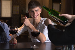 Happy young man drinking wine with friends Stock Images