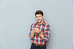 Happy young man in earphones listening to music from smartphone Royalty Free Stock Photos