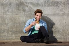 Happy young man eating asian food with chopsticks Stock Photos