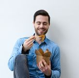 Happy young man eating asian food Stock Photos