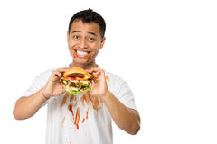 Happy young man eating a big burger Stock Photo