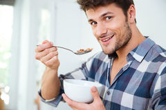 Happy young man eating cereals with milk at home. Portrait of happy young man in checkered shirt eating cereals with milk at home royalty free stock photo