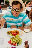 Happy young man eating food in hotel. All inclusive concept. Summer vacation. Having lunch with glass of wine and fruits Stock Images