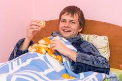Happy young man eats tangerines Stock Photos