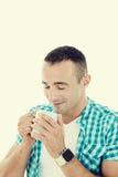 Happy young man enjoying hot beverage drinking coffee from mug royalty free stock image