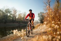 Free Happy Young Man Enjoying Late Afternoon Mountain Bike Ride By The River On A Clear Autumn Day Royalty Free Stock Photos - 165723458