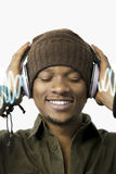 Happy young man enjoying music through headphones over white background Royalty Free Stock Photo