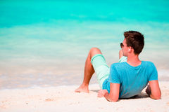 Happy young man enjoying the music on white sandy beach Stock Image