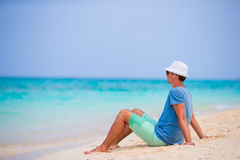 Happy young man enjoying the music on white sandy beach Stock Images