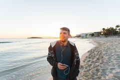Happy young man enjoying the music on white sandy beach. Travel, holidays, tourism and people concept Royalty Free Stock Photo