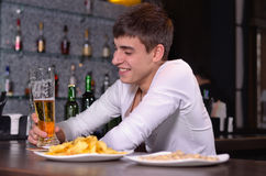 Happy young man enjoying a pint of beer. Sitting at a bar counter with plates of snacks in front of him royalty free stock photos