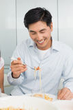 Happy young man enjoying spaghetti lunch in kitchen Royalty Free Stock Image