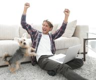 Happy young man exults with his dog sitting in the living room Stock Photos