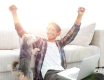 Happy young man exults with his dog sitting in the living room. The concept of home life Stock Photography