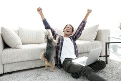Happy young man exults with his dog sitting in the living room Royalty Free Stock Photo
