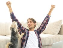 Happy young man exults with his dog sitting in the living room Royalty Free Stock Photography