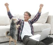 Happy young man exults with his dog sitting in the living room Royalty Free Stock Photos
