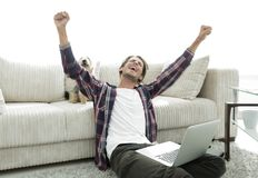 Happy young man exults with his dog sitting in the living room Stock Image