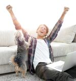 Happy young man exults with his dog sitting in the living room. The concept of home life Stock Images