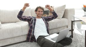 Happy young man exults with his dog sitting in the living room. The concept of home life Royalty Free Stock Image