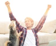 Happy young man exults with his dog sitting in the living room. The concept of home life Royalty Free Stock Images