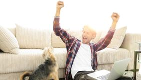 Happy young man exults with his dog sitting in the living room. The concept of home life Royalty Free Stock Photo