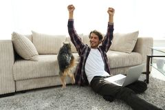 Happy young man exults with his dog sitting in the living room. The concept of home life Stock Photos