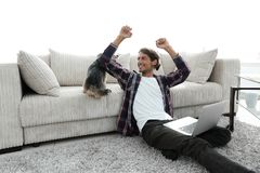 Happy young man exults with his dog sitting in the living room. The concept of home life Stock Image