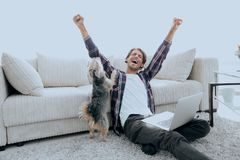 Happy young man exults with his dog sitting in the living room. The concept of home life Stock Photo