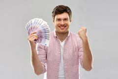 Happy young man with fan of euro money. Money, finance, business and people concept - happy young man with fan of five hundred euro bank notes over grey royalty free stock images